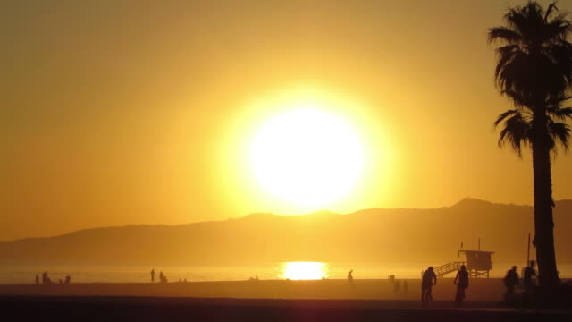 Time Lapse of a massive orange sunset over the ocean and mountains