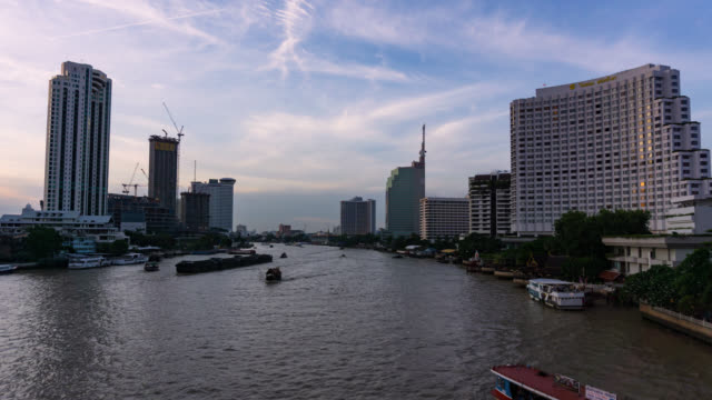Time lapse of Bangkok cityscape river side with Chao praya river at the sunset with the day to night concept