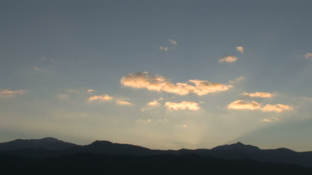 WS Time lapse of clouds in sky over mountains at sunrise