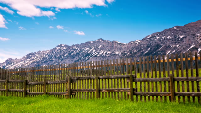 Time lapse of clouds moving over mountains and fence