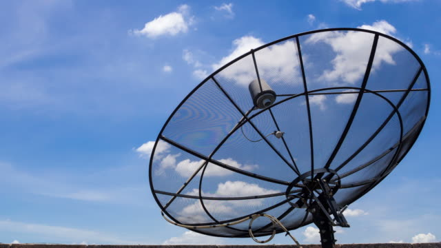 Time Lapse of clouds moving over satellite dish antennas