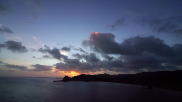 Time lapse of clouds passing over promontory at sunset / Great Barrier Island, New Zealand
