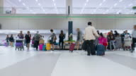 Time Lapse of Crowd collecting baggage from airport conveyer belt