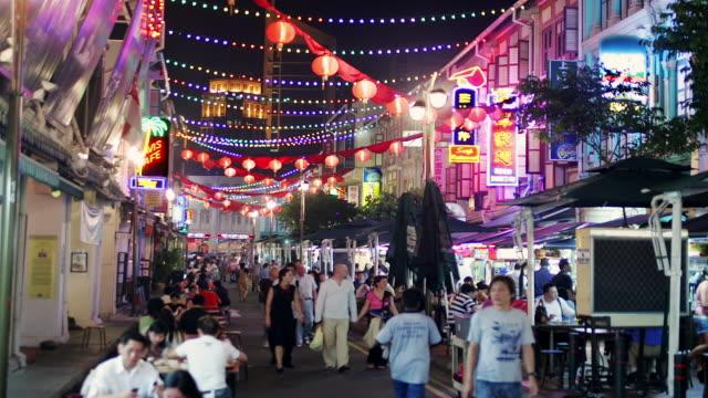 Time lapse of crowd walking under lanterns strung over street market in Chinatown at night / Singapore