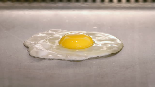 Time lapse of hands cracking egg onto grill / zoom in to frying egg