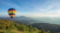 Time lapse of hot air balloon flying over high mountain