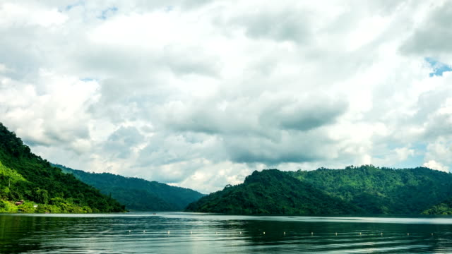 Time lapse of Lake and moving cloudy sky with green mountains background