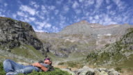 Time lapse of man relaxing in mtn meadow with clouds overhead