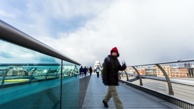 LONDON - CIRCA 2012: Time lapse of Millennium bridge with storm couds and sun
