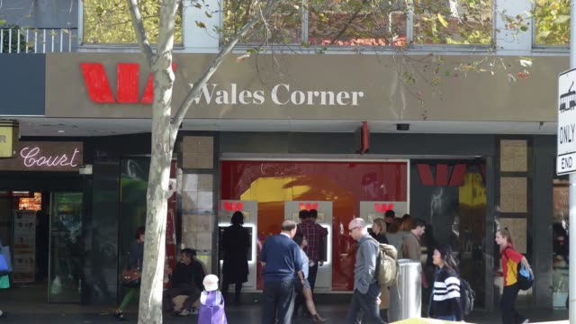 WS time lapse of pedestrians walking past Westpac Banking Corp ATM machines while trams and buses pass by
