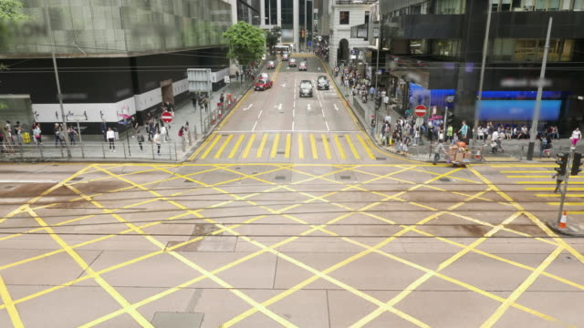 Time lapse of people and vehicles at pedestrian crossing intersection on busy road