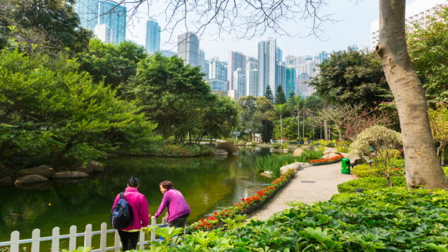 Time Lapse of people in Hong Kong Park, skyscrapers in background