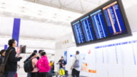 Time Lapse of people looking at information screen in modern airport building