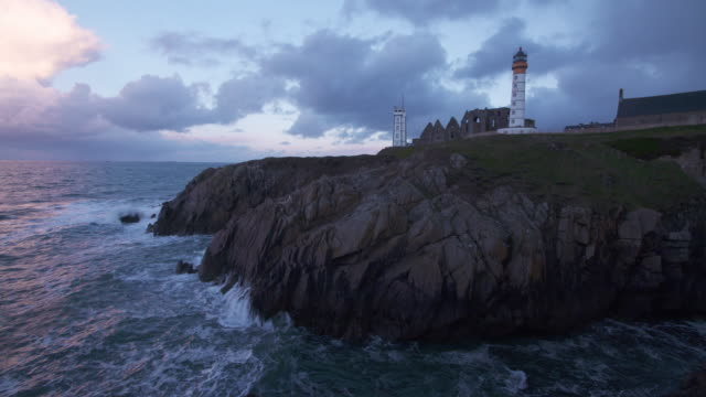 Time Lapse of Saint-Mathieu lighthouse (Pointe Saint-Mathieu) with rocky coastline, moving clouds short after sunrise.