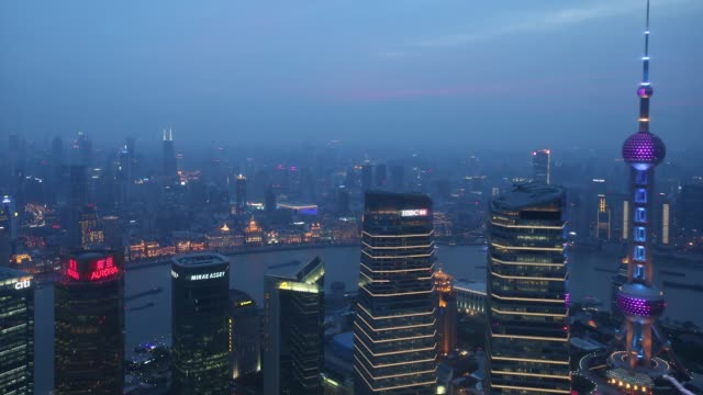 Time lapse of Shanghai city skyline from sunset as the Oriental Pearl Radio TV Tower right and commercial buildings are illuminated in Shanghai China...