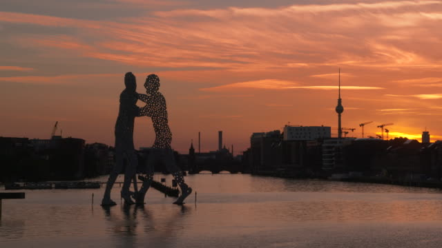 Time Lapse of Spree River with Molecule Men, Oberbaum bridge and Berlin television tower at sunset. Spree River, Berlin, Germany.