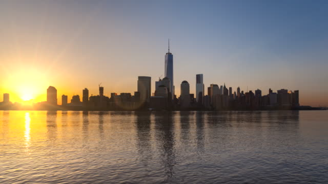 Time Lapse of sun rising over Manhattan financial district skyline, night to day