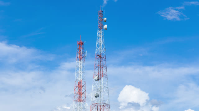 Time lapse of telecom pole with clouds move and blue sky background