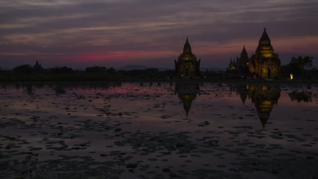 Time lapse of the sunset over a pond in Bagan, Myanmar with gold pagodas