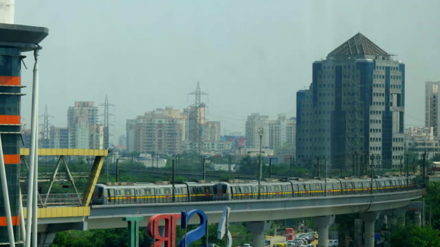 A time lapse of two Delhi Metro trains criss-crossing each other just before HUDA Metro station in Gurgaon, with the city skyline in the back