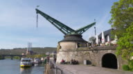 Time Lapse. Old historic harbour crane (quay crane) in Würzburg at the Main river. People walking.