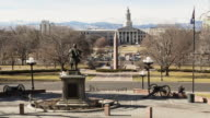A time lapse on a sunny, winter afternoon from the steps of the Colorado State Capitol of Civic Center Park with the Colorado state flag waving in the wind in the foreground, an obelisk in the midground, and the Denver County Courthouse in the background