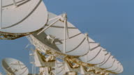 time lapse orderly rows of VLA (Very Large Array) radio telescope dishes moving / New Mexico