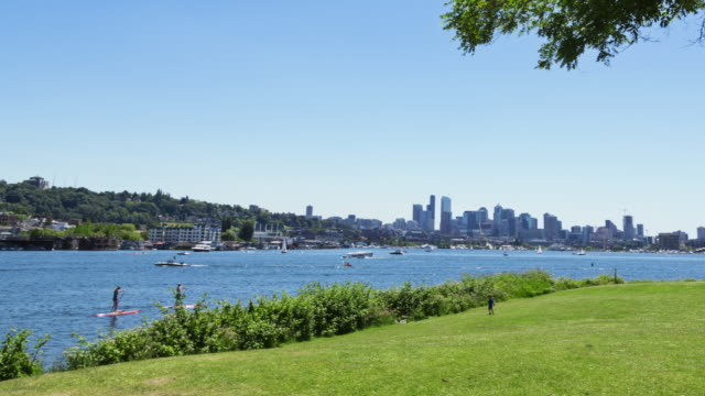 W/S time lapse panning through Gas Works Park where people picnic on a sunny summer day, with Lake Union and the Seattle skyline
