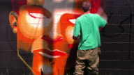 MS time lapse REAR VIEW young man spraypainting mural of face (self portrait) on black wall / Los Angeles