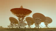 ORANGE time lapse rows of VLA (Very Large Array) radio telescope dishes / sunset to night / New Mexico