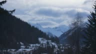 Time lapse sequence shows snowcovered mountain peaks moving clouds daylight changing to dusk above the town of Davos Switzerland on Sunday Jan 19...