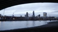 A time lapse sequence shows view of pedestrians walking along the shore of the River Thames and office skyscrapers and construction cranes on the...