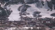 Time lapse shadows play on a snow covered mountain and a village below.