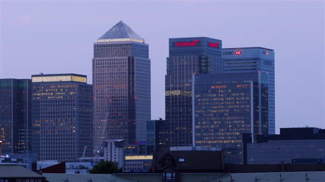 Time lapse shot of Canary Wharf Tower, Citigroup Centre, and HSBC Tower lighting up as dusk turns to night / Canary Wharf, London, England