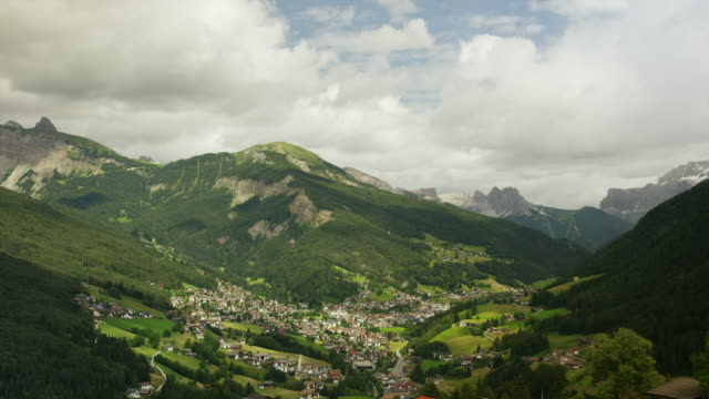 Time lapse shot of shadows passing over town in remote mountain valley / St. Ulrich Ortisei, Dolomites, Italy