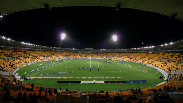 Time lapse shot of Westpac Stadium filling with spectators at dusk / rubgy game / stadium emptying and lights going out at night / Wellington, New Zealand