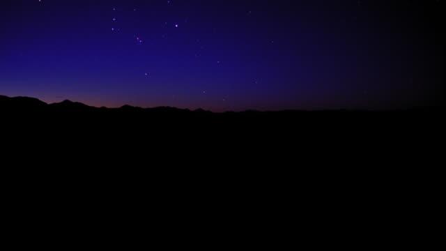 PAN time lapse stars rising over mountains / sky brightening to white / Aspen, Colorado