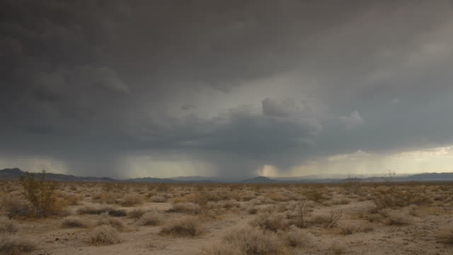 Time lapse storm clouds and lightning on a desert plain.
