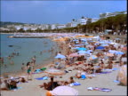 time lapse sunbathers + swimmers on crowded beach / Cannes, France