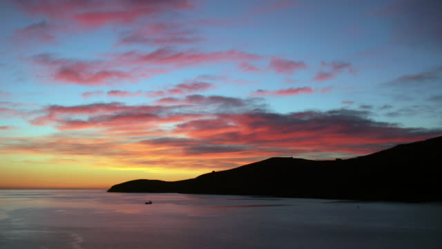 Time lapse sunrise at entrance to Lyttelton Harbour / ship in water and surrounding hills silhouetted / Lyttelton, New Zealand