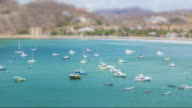 Time lapse tilt shift at a bay in Pacific sea. Boats miniature effect at the San Juan del Sur Nicaragua idylic beach. Coastline from aerial point of view.