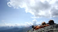 Time lapse view of clouds lifting above sleeping hikers