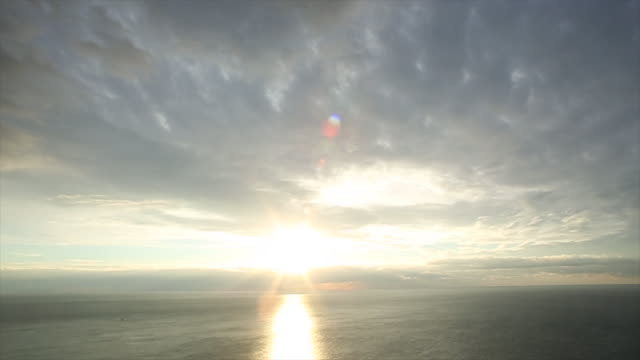 Time lapse view of clouds streaming above sea, sunrise