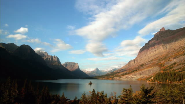 Time lapse wide shot clouds passing over lake at foot of Rocky Mountains / Glacier National Park, Montana