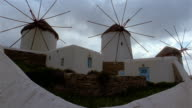 Time lapse wide shot clouds passing over motionless windmills / Mykonos, Greece
