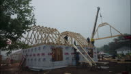 Time lapse wide shot construction crew building house / finishing before nightfall