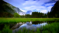 Time lapse wide shot lake with mountains and trees in background / Yosemite National Park, California