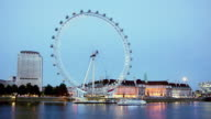 Time lapse wide shot Millenium Wheel turning from dusk to night with boats passing by on Thames/ London
