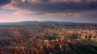 Time lapse wide shot pan rock formations in Bryce Canyon with clouds forming in sky / Utah