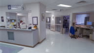 Time lapse wide shot pan staff moving around in reception area of critical care unit of hospital / Houston, Texas